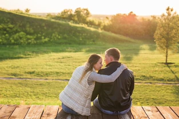 Conceito de pessoas, relações e sentimentos - jovem casal apaixonado se abraçando no parque outono