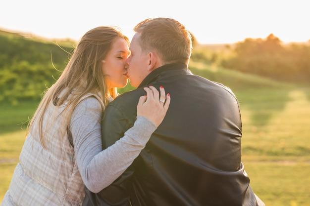 Conceito de pessoas, relações e sentimentos - jovem casal apaixonado se beijando no parque outono
