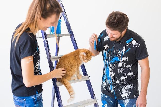 Conceito de pessoas, renovação, animal de estimação e reparo - retrato de um homem engraçado e uma mulher com um gato fazendo redecoração em um apartamento