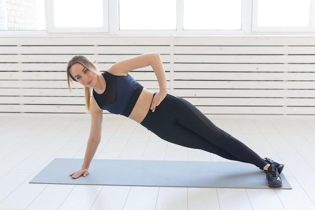 Conceito de pessoas, saúde e fitness - mulher desportiva fazendo prancha lateral no tapete cinza.