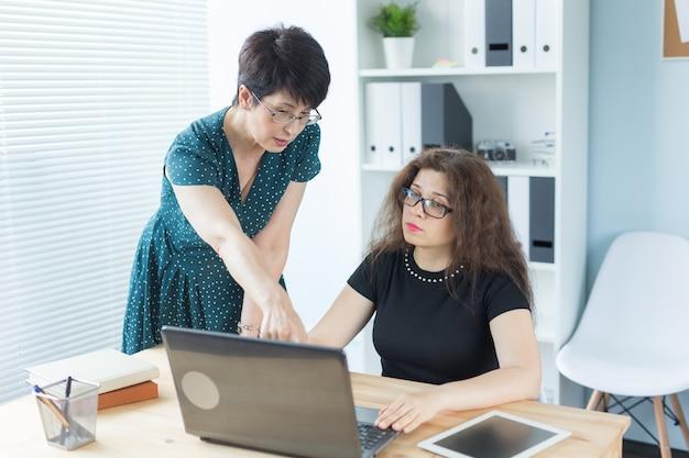 Conceito de pessoas, tecnologia e comunicação de negócios - senhora de meia idade ajudando sua colega