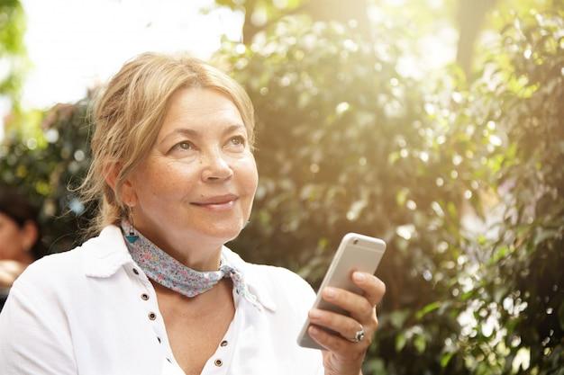 Conceito de pessoas, tecnologia e comunicação. encantadora mulher sênior com cabelos loiros usando telefone inteligente genérico