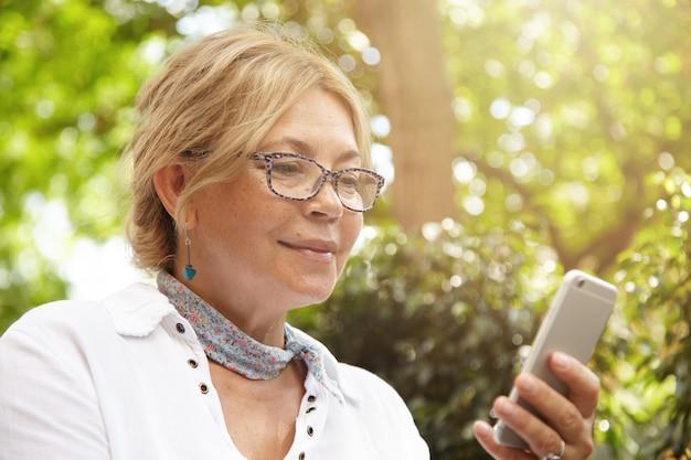 Conceito de pessoas, tecnologia e comunicação. escritora sênior atraente em óculos usando telefone inteligente genérico para publicar um novo post nas redes sociais, gastando seu tempo livre em blogs