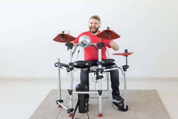 Conceito de pessoas, tempo livre e hobby - baterista de homem barbudo tocando o tambor.