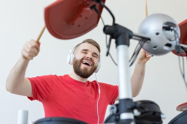 Conceito de pessoas, tempo livre e hobby - baterista masculino legal sobre o fundo do quarto branco.