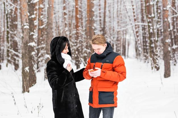 Conceito de pessoas, temporada, amor, tecnologia e lazer - casal feliz tirando foto com selfie stick no smartphone sobre o fundo do inverno