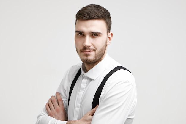 Conceito de pessoas, trabalho, emprego, carreira e emprego. foto de um atraente empresário próspero jovem e confiante posando no estúdio com os braços cruzados e olhando para a câmera com um sorriso confiante