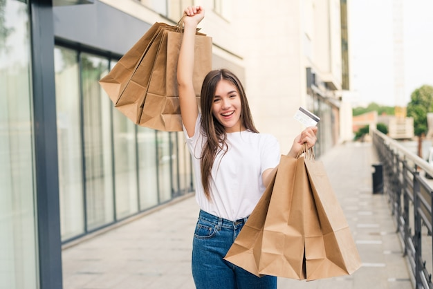 Conceito de pessoas, venda e consumismo - close-up de uma mulher feliz com sacolas de compras e cartão de crédito na rua da cidade