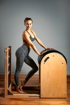 Conceito de pilates, fitness, esporte, treinamento e pessoas - mulher fazendo exercícios em um pequeno barril. correção do aparelho impelente, postura correta.