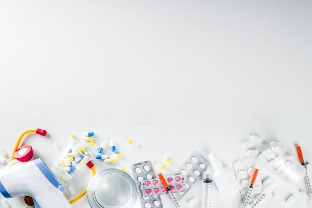 Conceito de pílulas de medicina farmacêutica, vários comprimidos, comprimidos e cápsulas variadas com seringas médicas, termômetro e copo d'água, cópia de maquete de espaço, flatlay