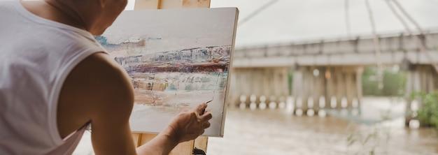 Conceito de pintura artística, o pintor está pintando como uma ponte sobre uma cena de pintura.