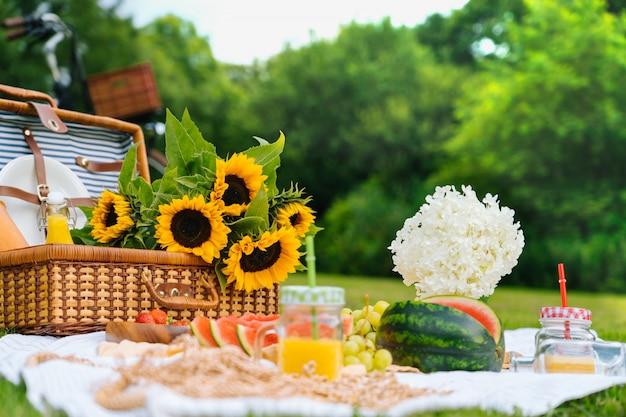 Conceito de piquenique de verão em dia ensolarado com flores de melancia, frutas, bouquet de hortênsias e girassóis.