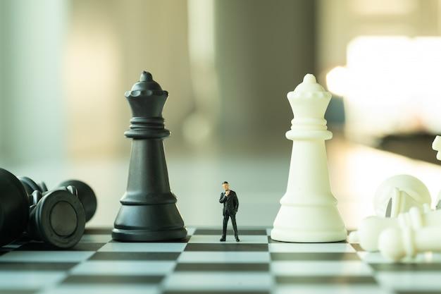 Conceito de planejamento de negócios. figura do pequeno empresário em pé e andando no tabuleiro de xadrez com peças de xadrez.