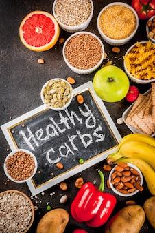 Conceito de plano de fundo de alimentos diet, produtos de carboidratos saudáveis (carboidratos) - frutas, legumes, cereais, nozes, feijão, fundo de concreto azul escuro vista superior espaço de cópia