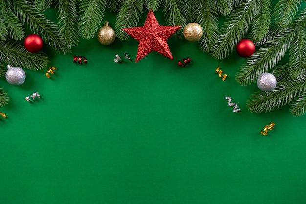 Conceito de plano de fundo de natal. vista superior da decoração de natal, estrela, ramos de abeto vermelho sobre fundo verde. copie o espaço.