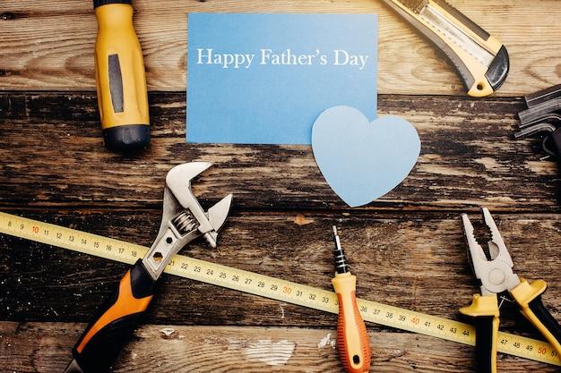 Conceito de plano de fundo do dia do pai feliz. vista superior de ferramentas úteis de construção no fundo de madeira.