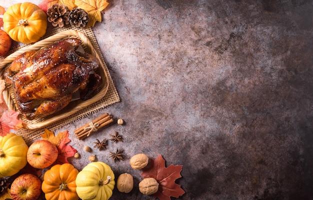 Conceito de plano de fundo do jantar de ação de graças com peru assado e folhas caídas de todos os pratos de acompanhamento