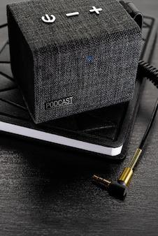 Conceito de podcast. sem fio, pequena coluna no livro (blonote) com um conector de cabo de áudio de 3,5 mm.