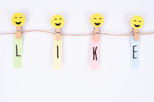 Conceito de polegar para cima. perto de um smiley alegre segurando uma parede branca isolada de palavras