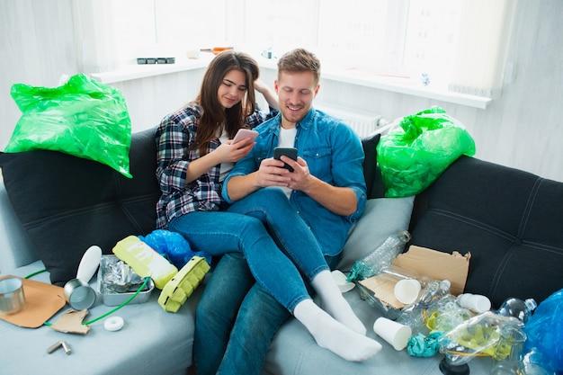 Conceito de poluição ambiental. casal no sofá na sala de estar. há muito lixo, resíduos de plástico por aí.