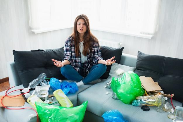 Conceito de poluição ambiental. jovem chocada. ela não sabe o que fazer com a poluição de seu apartamento e do mundo inteiro