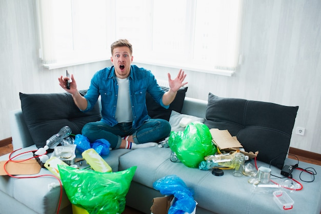 Conceito de poluição ambiental. jovem chocado. ele não sabe o que fazer com a poluição de seu apartamento e do mundo inteiro