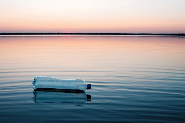 Conceito de poluição, criativo. uma garrafa de plástico flutuando no oceano
