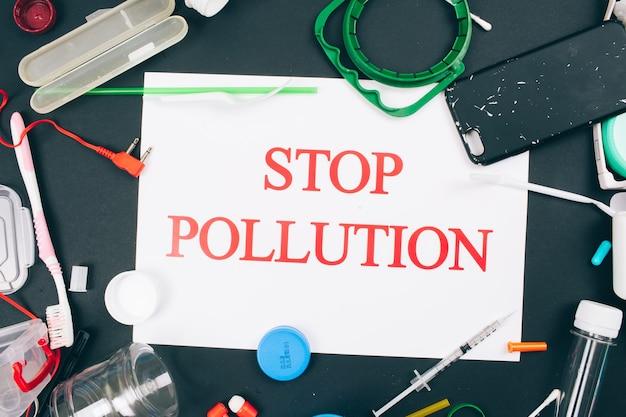 Conceito de poluição de plástico recusar plástico singleuse papel com palavras pare a poluição no centro de resíduos plásticos coloridos diferentes de uso único em fundo escuro