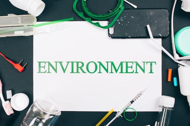 Conceito de poluição de plástico. seja livre de plástico. papel com a palavra ambiente no centro de resíduos plásticos coloridos de uso único. um problema ambiental, diretiva da ue. vista do topo
