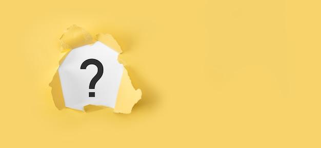 Conceito de ponto de interrogação. papel amarelo rasgado com ponto de interrogação na superfície amarela.