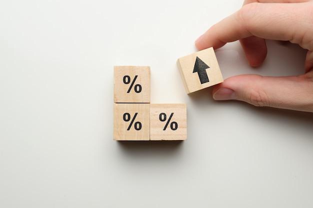 Conceito de porcentagem em finanças, aumentando com ícones em blocos de madeira.