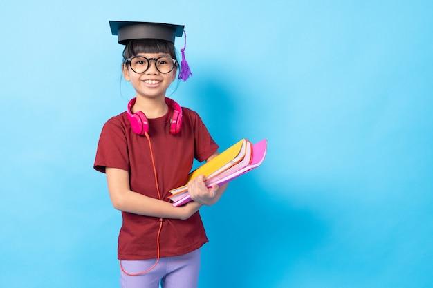 Conceito de pós-graduação e educação, estudante de criança asiática menina tailandesa com livros e fone de ouvido usando chapéu de bacharel