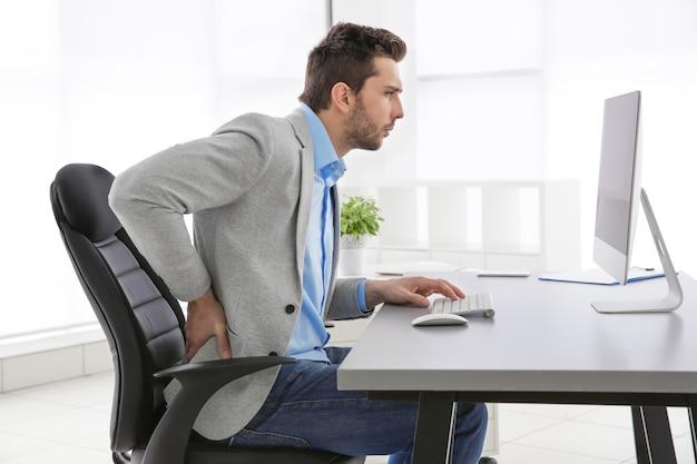 Conceito de postura incorreta. homem sentado à mesa do escritório