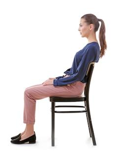 Conceito de postura incorreta. jovem mulher sentada na cadeira contra um fundo branco
