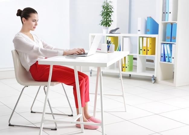 Conceito de postura incorreta. mulher jovem sentada à mesa em um quarto moderno