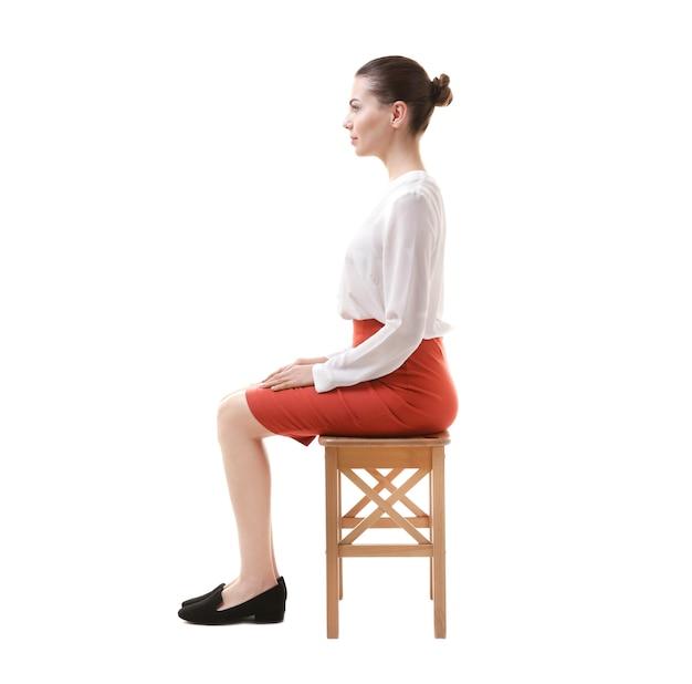 Conceito de postura incorreta. mulher jovem sentada em um banquinho contra um fundo branco