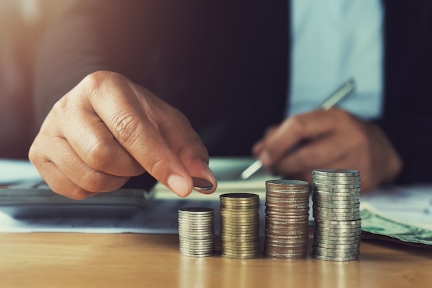 Conceito de poupar dinheiro. mão segurando moedas colocando pilha na mesa no escritório
