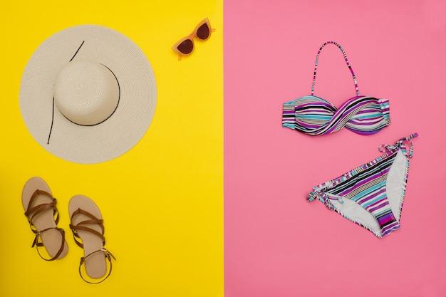 Conceito de praia. chapéu, sandálias, maiô e óculos de sol femininos