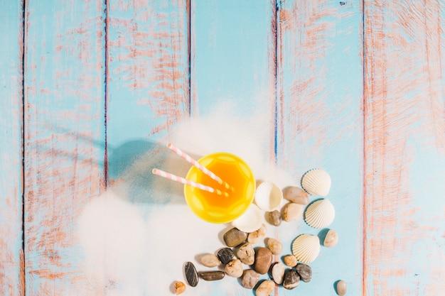 Conceito de praia com copo de suco na placa de madeira