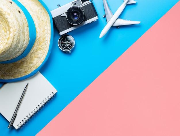 Conceito de praia de viagens de verão com moda de viagens de verão e objetos na vista superior rosa liso azul