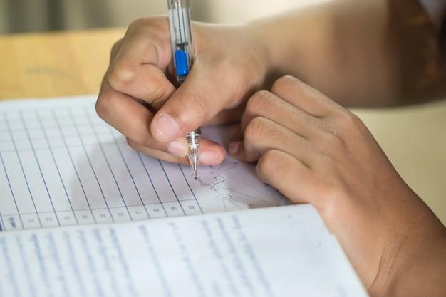 Conceito de prática de arte educacional: colégio man hands, estudante universitário segurando um lápis para testar a folha de papel de desenho e escrita e exercícios na sala de aula de arte