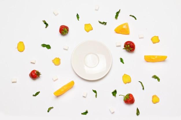 Conceito de prato branco vazio, cubos de açúcar, morangos, fatias de gengibre, laranja e folhas de hortelã