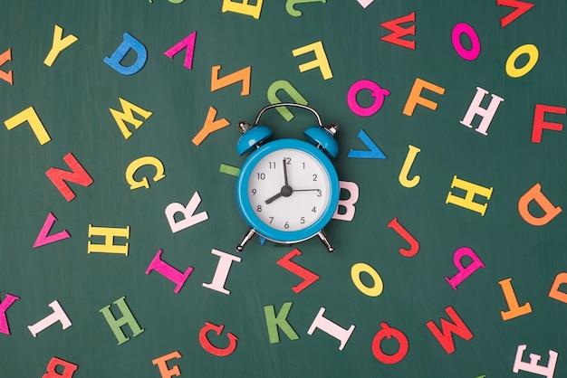 Conceito de prazo de tarefa. foto de visão superior acima do relógio azul isolada no quadro verde com letras coloridas