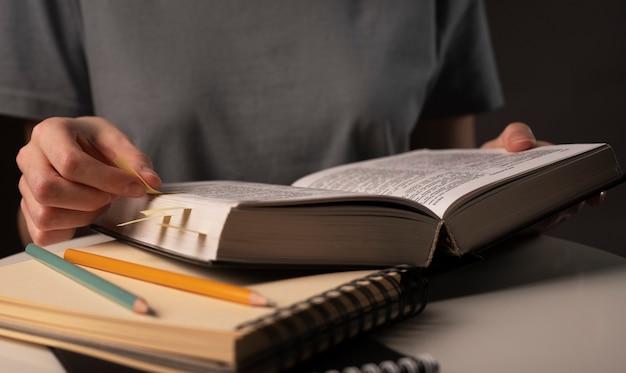 Conceito de preparação para exame, aprendizagem, estudo e educação à noite, fazendo anotações, marcadores no livro didático.