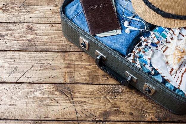 Conceito de preparações de viagem com mala, roupas e acessórios em uma velha mesa de madeira. vista superior copie o espaço
