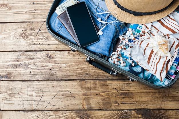 Conceito de preparações de viagem com mala, roupas e acessórios em uma velha mesa de madeira.