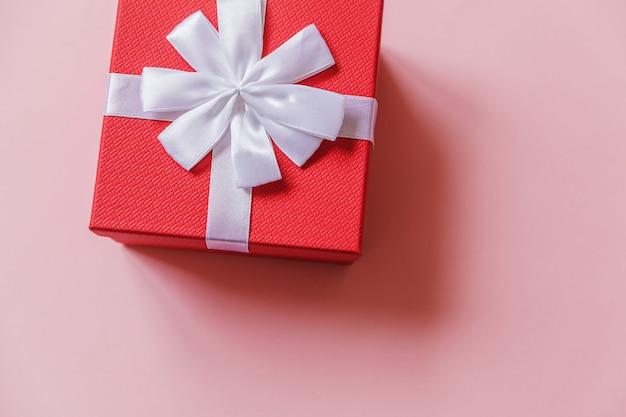 Conceito de presente de aniversário de ano novo de natal. caixa de presente vermelha de design minimalista isolada em fundo rosa