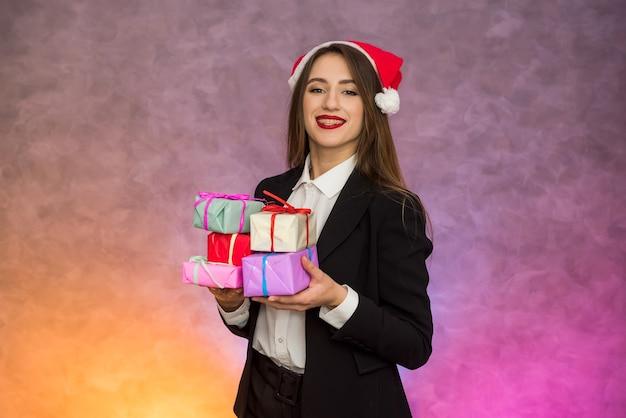 Conceito de presentes de natal. linda mulher segurando caixas de presentes coloridas