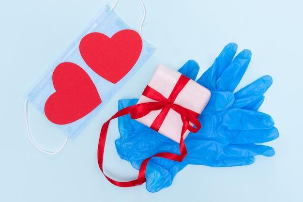 Conceito de presentes seguros. caixa de presente com uma fita vermelha em luvas de proteção azuis e dois corações de amor de papel vermelho