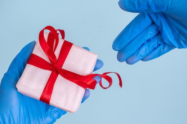 Conceito de presentes seguros. uma mão masculina com uma luva médica azul dá um presente para uma mão feminina com uma luva médica azul
